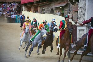 Riders racing at El Palio horse race festival, Piazza del Campo, Siena